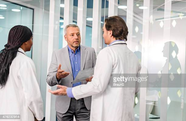 Businessman talking with two doctors about new reports.