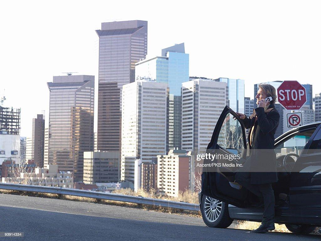 Businessman talks on cell phone beside car, city : Stock Photo