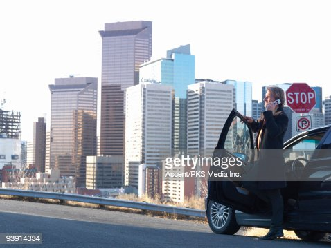 Businessman talks on cell phone beside car, city : Stock Photo