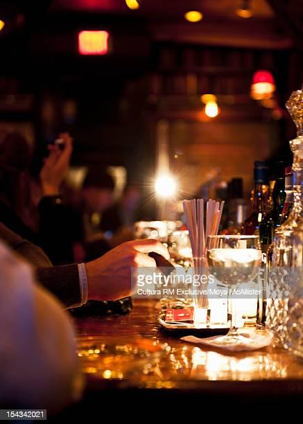 Businessman tapping cigar at bar