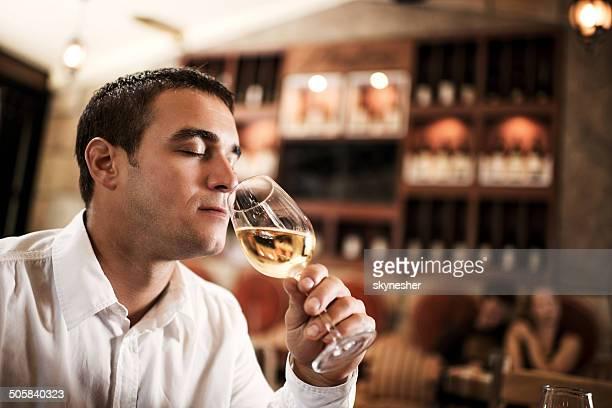 Businessman tasting wine in a bar.