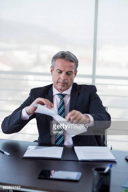 Businessman tearing a document