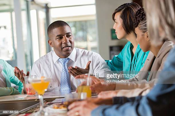 Businessman telling story to friends at restaurant bar