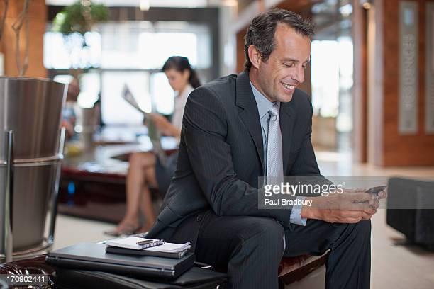 Homme d'affaires de SMS sur téléphone portable dans le hall de l'hôtel