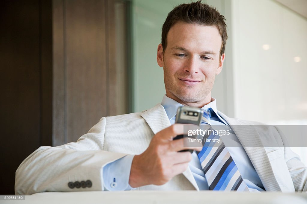 Businessman text messaging on cell phone : Foto de stock