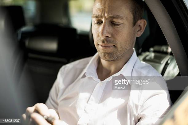 Businessman text messaging through mobile phone in taxi