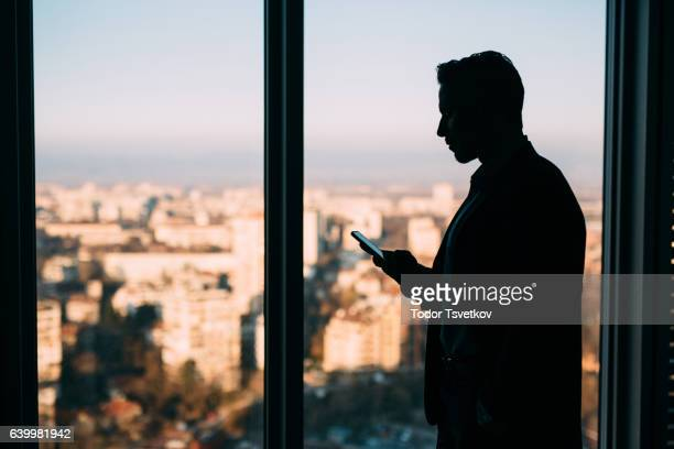 Businessman Texting At The Window