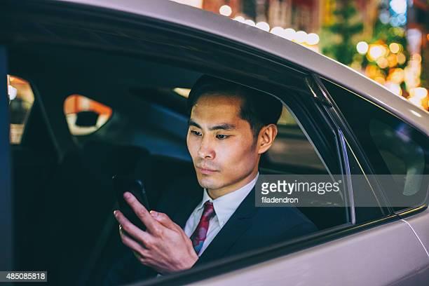 Businessman texting in a car