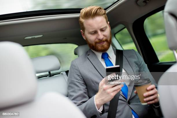 Businessman texting message on the back seat