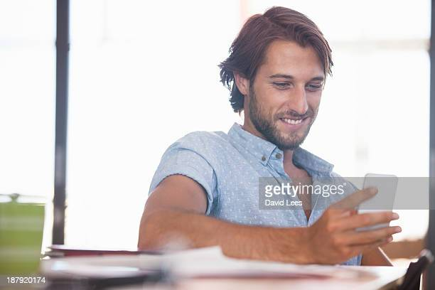 Businessman texting on cell phone in modern office