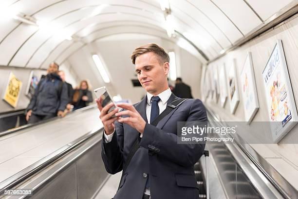 Businessman texting on escalator, London Underground, UK