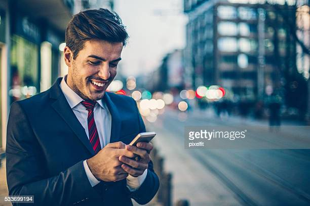 Businessman texting outdoors in the evening