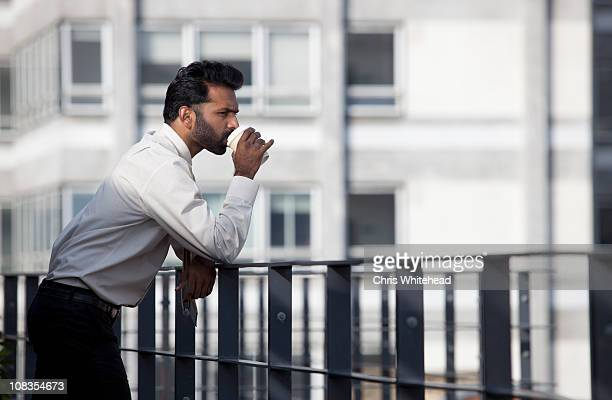 Businessman thinking and drinking coffee