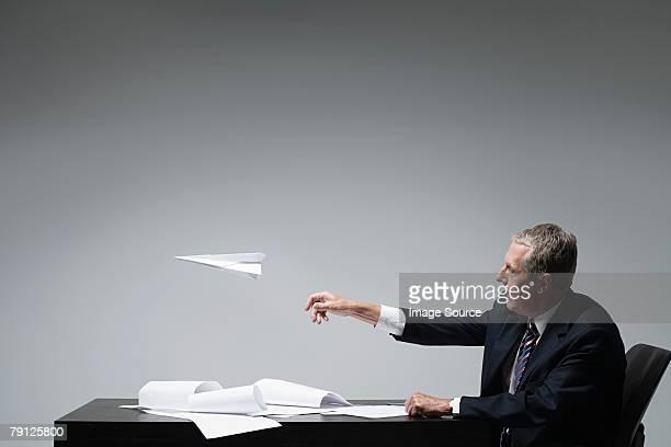 Ein Geschäftsmann werfen Papier Flugzeug