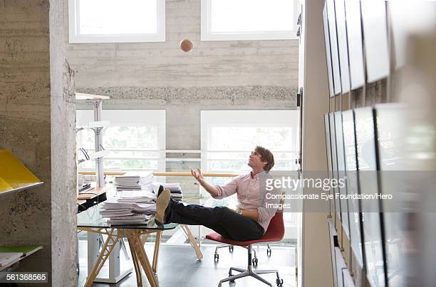 Businessman throwing ball in air in office