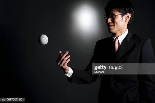 Businessman throwing baseball, studio shot