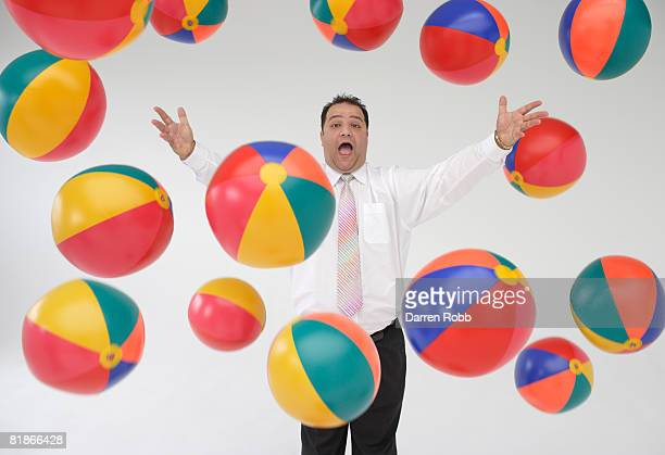 Businessman throwing beach balls in the air