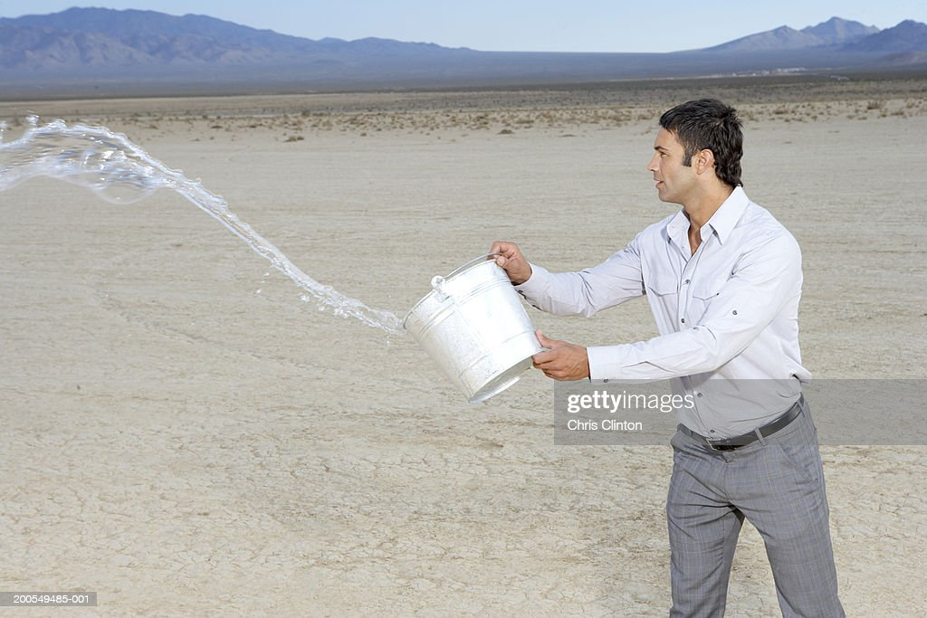 Businessman throwing bucket of water on dry lake bed