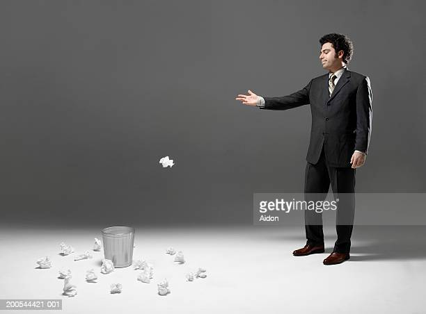 Businessman throwing crumpled paper into waste basket, studio shot
