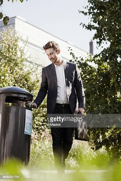 Businessman throwing garbage in bin at park