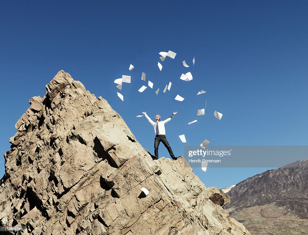 Businessman throwing paperwork from mountain top : Stock Photo