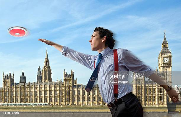 Businessman throws discus by Houses of Parliament.