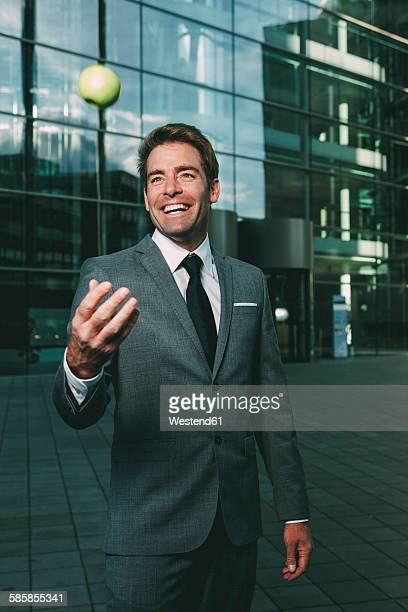 Businessman tossing a green apple outside office building