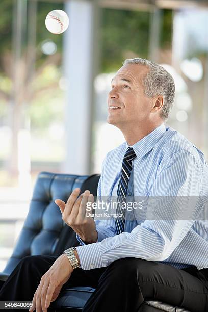 Businessman tossing baseball
