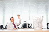 Businessman tossing crumpled paper at waste bin