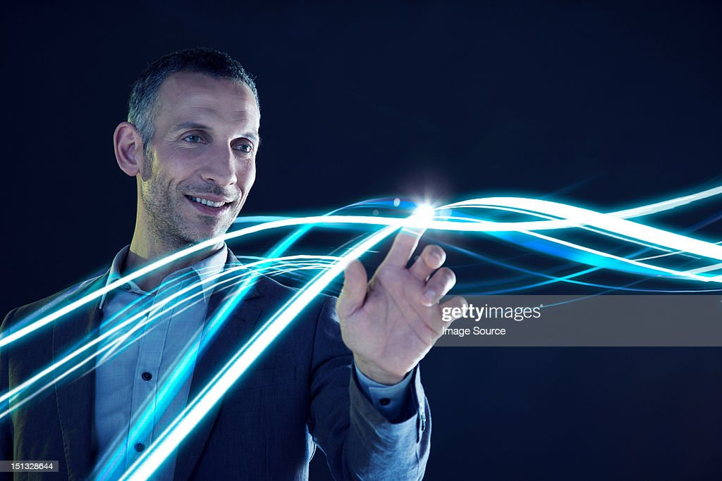 Businessman touching lines of light : Stock Photo
