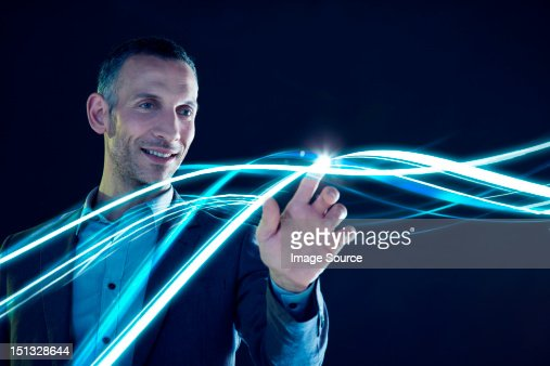 Businessman touching lines of light