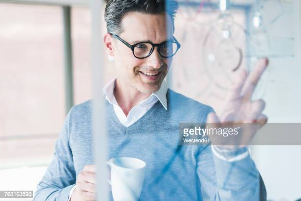 Businessman touching transparant projection screen in office