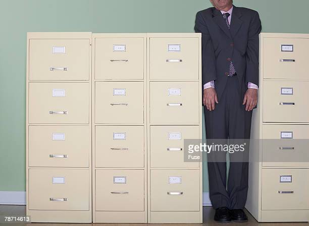Businessman Trapped Between Filing Cabinets