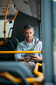 Businessman commuting to work by bus and working with a digital touch screen tablet