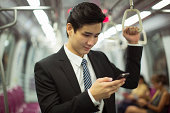 Businessman travelling on subway, texting.