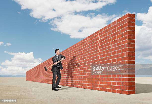 Businessman trying to break down barrier created by brick wall