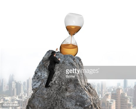 Businessman trying to grab hourglass on peak : Stock Photo