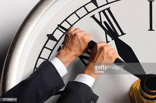 Businessman trying to hold back the hands on a clock