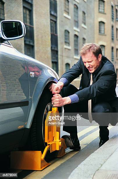 Businessman Trying to Remove a Wheel Clamp From His Car