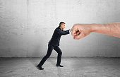 Businessman trying to resist a huge male fist and move it away on a grey background. Containing market pressure. Being competitive. Protecting a small business.