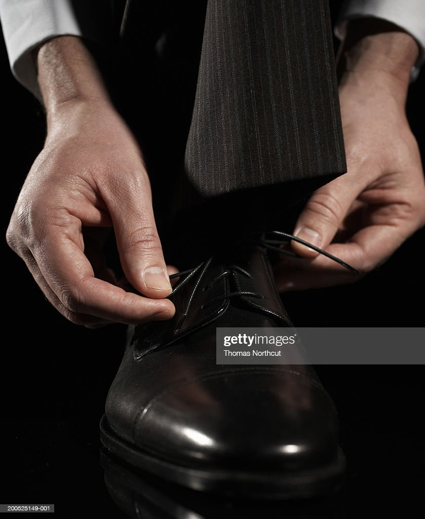 Businessman tying shoe, low section : Stock Photo