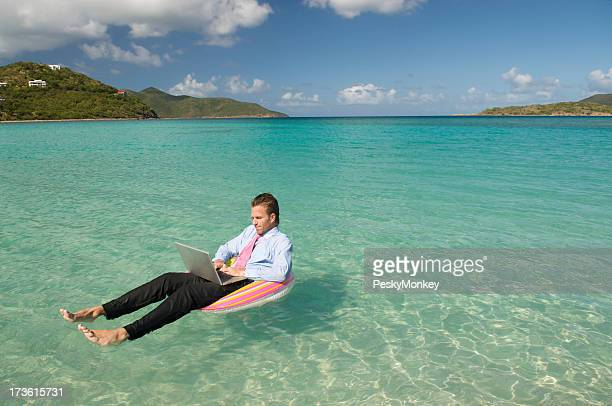 Businessman Typing Floating in Tropical Waters