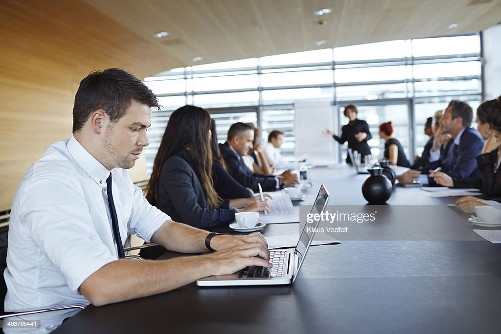 Businessman typing on laptop at big presentation : Stock Photo