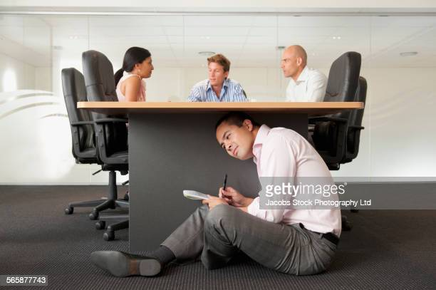 Businessman under desk eavesdropping in office meeting