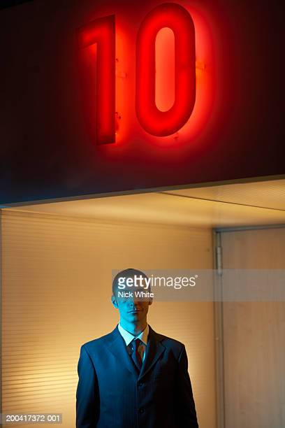 Businessman under neon '10' sign, portrait