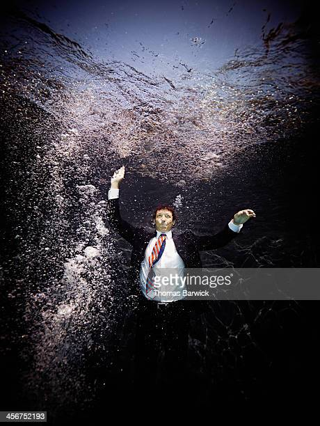 Businessman underwater in suit swimming to surface