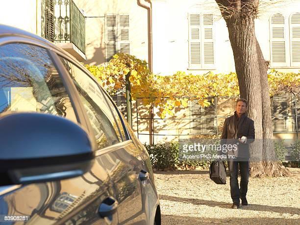 Businessman unlocks car while walking from villa