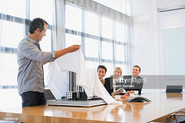 Businessman unveiling model building to co-workers