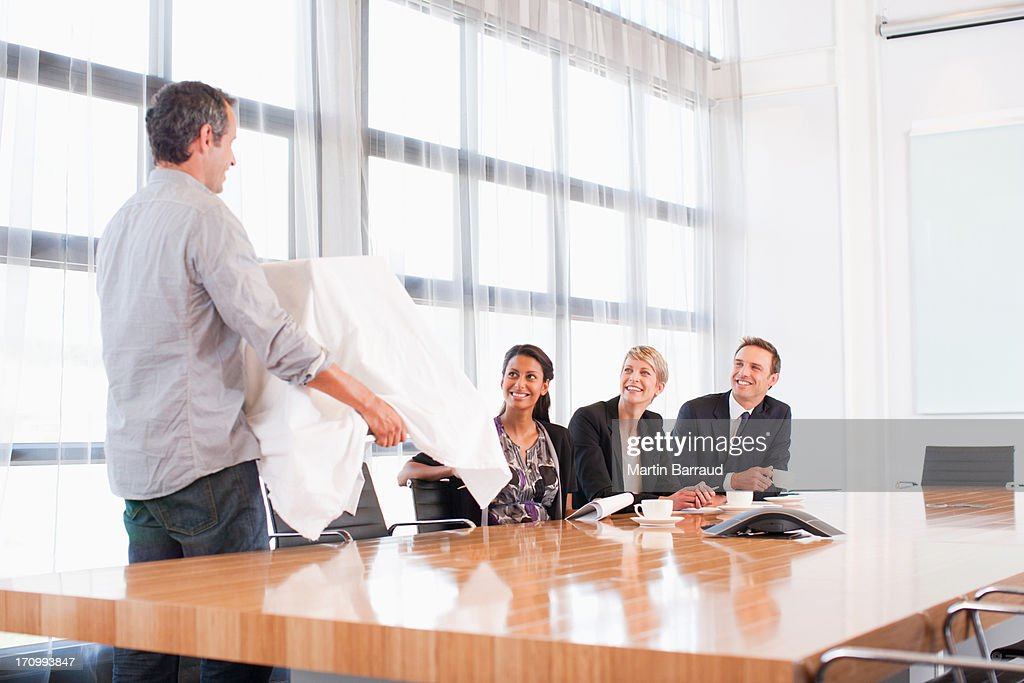 Businessman unveiling model building to co-workers : Stock Photo