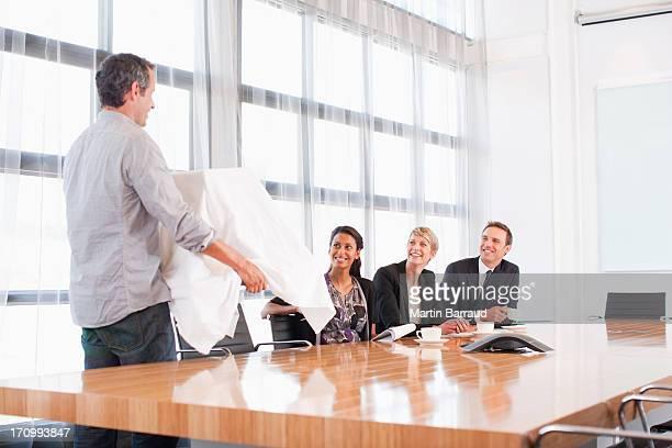 Homme d'affaires se lève pour dévoiler le modèle construction des collègues